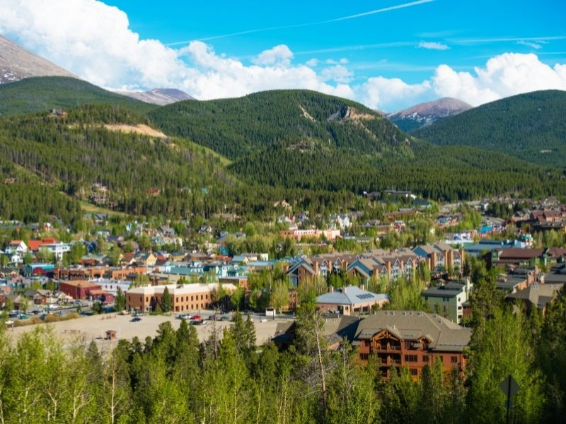 The resort town of Breckenridge in summer with trees, mountains and lots of ski chalets and other buildings