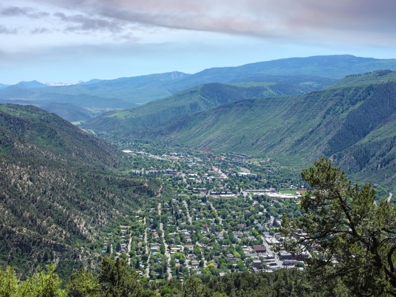 city of glenwood springs below in the valley floor between mountains in colorado in summer