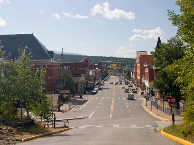 The Main street of downtown Leadville, Colorado with red brick architecture on a sunny day in the colorado mountains and mostly empty streets.