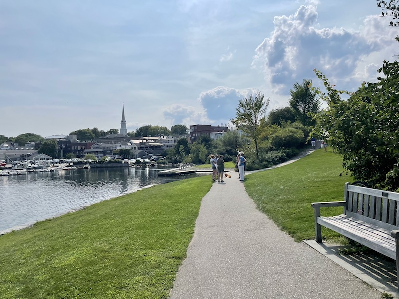 bench, walkway, and harbor with church steeple in the town skyline in the background on a partly cloudy day in summer in camden maine