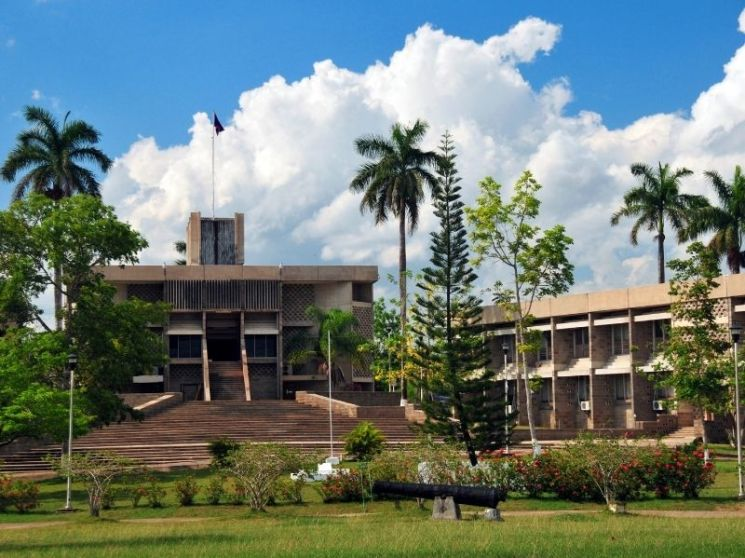 parliament building in belmopan belize with trees and flowers and steps