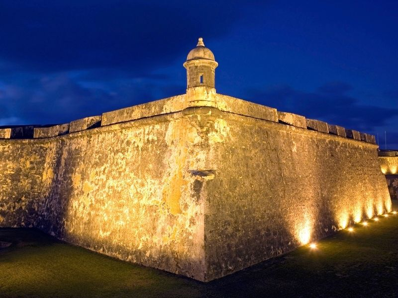 lit up fort of el morro at night with a dark blue sky