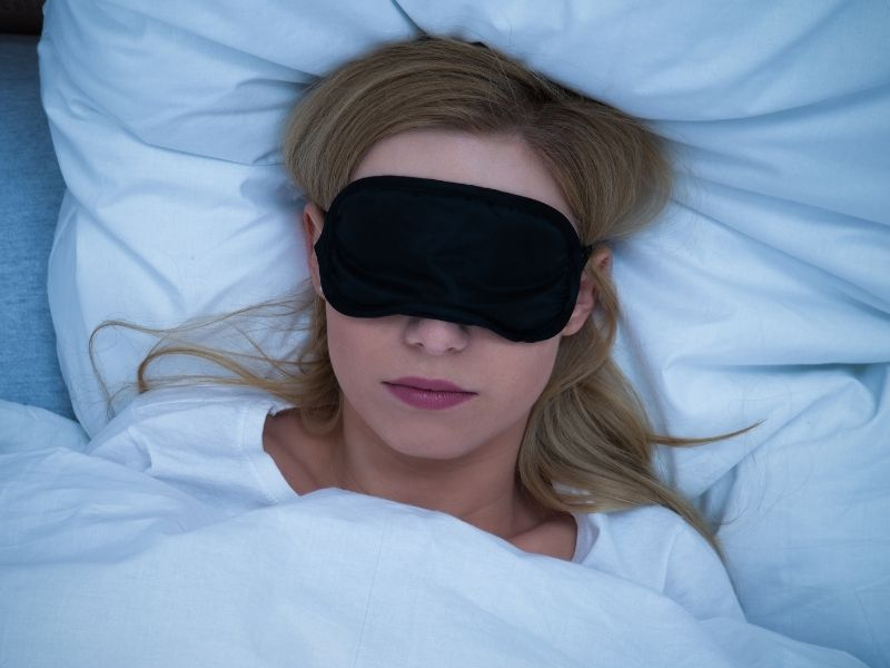 woman wearing an eye mask laying in bed