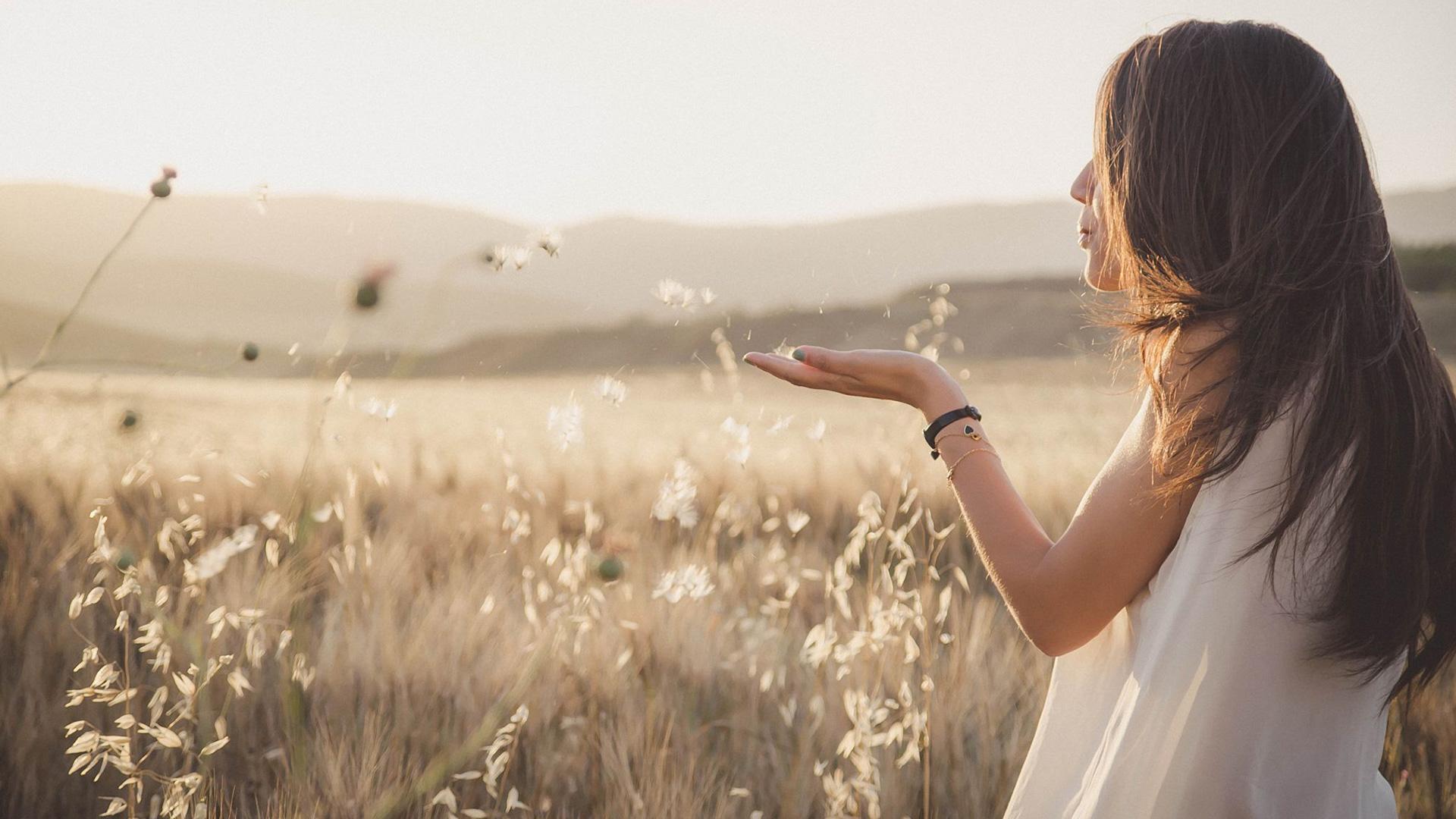 Woman Blowing Flower In Field