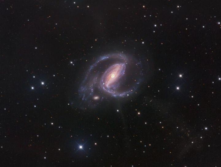Imagem de campo profundo da galáxia Seifert NGC 1097 mostra seus 4 jatos que forma um X. Crédito: Robert Gendler.