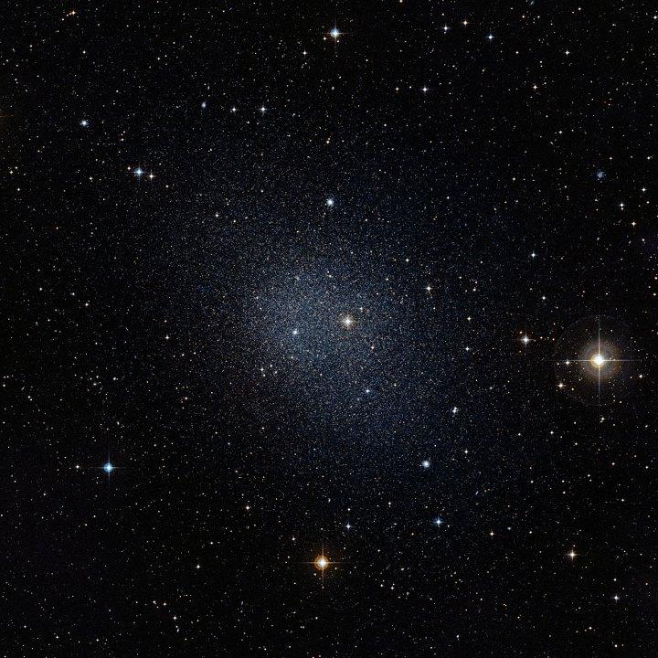 A galáxia anã de Fornax (Fornalha), vizinha da Via Láctea, foi alvo da busca por estrelas primitivas. Crédito: ESO/Digitized Sky Survey 2