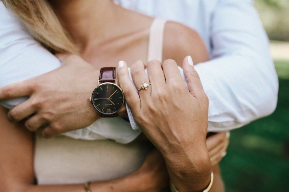 engagement ring and watch on ethical bride and groom