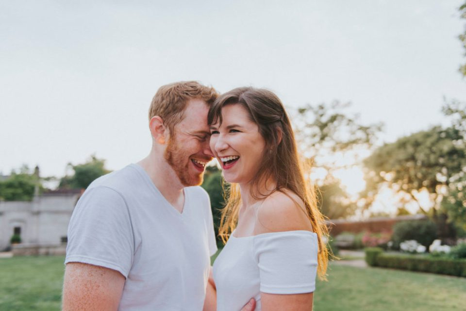 a couple smiles and laughs against sky and green background