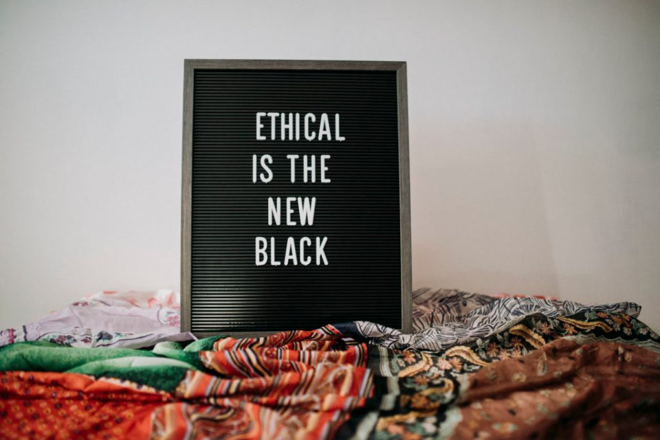 "Sign that reads ""Ethical is the new black"" against white wall"