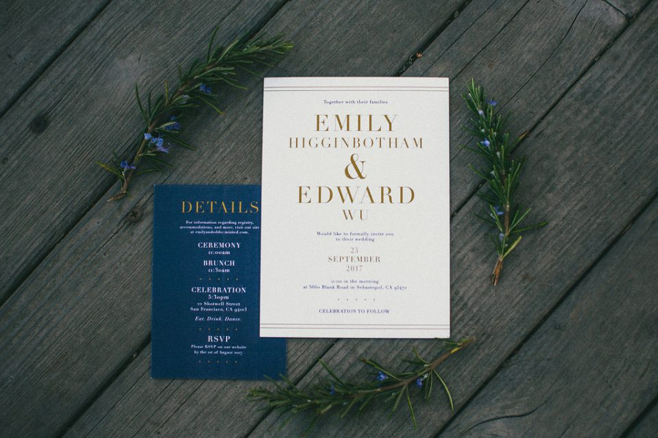 wedding invitations laid out on wood, surrounding by leaves