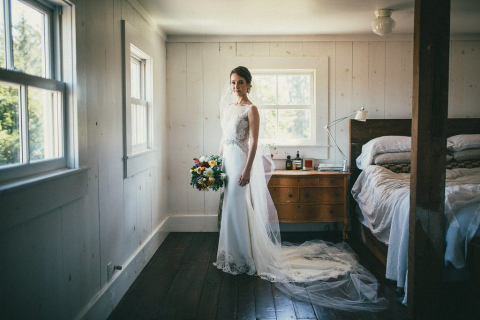 bride standing in a bedroom, holding her bouquet of flowers