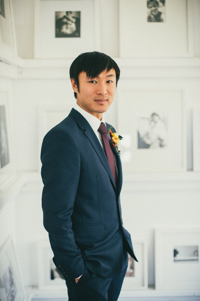 portrait of the groom in front of white wall