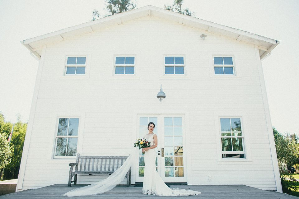 bride poses in front of white house