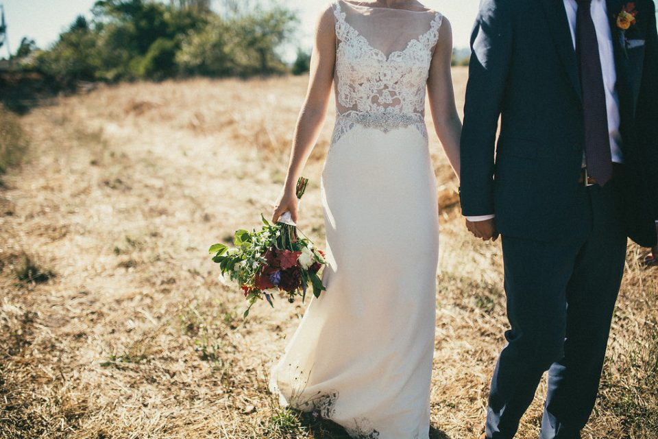 bride and groom walk through field, bride holding bouquet of flowers
