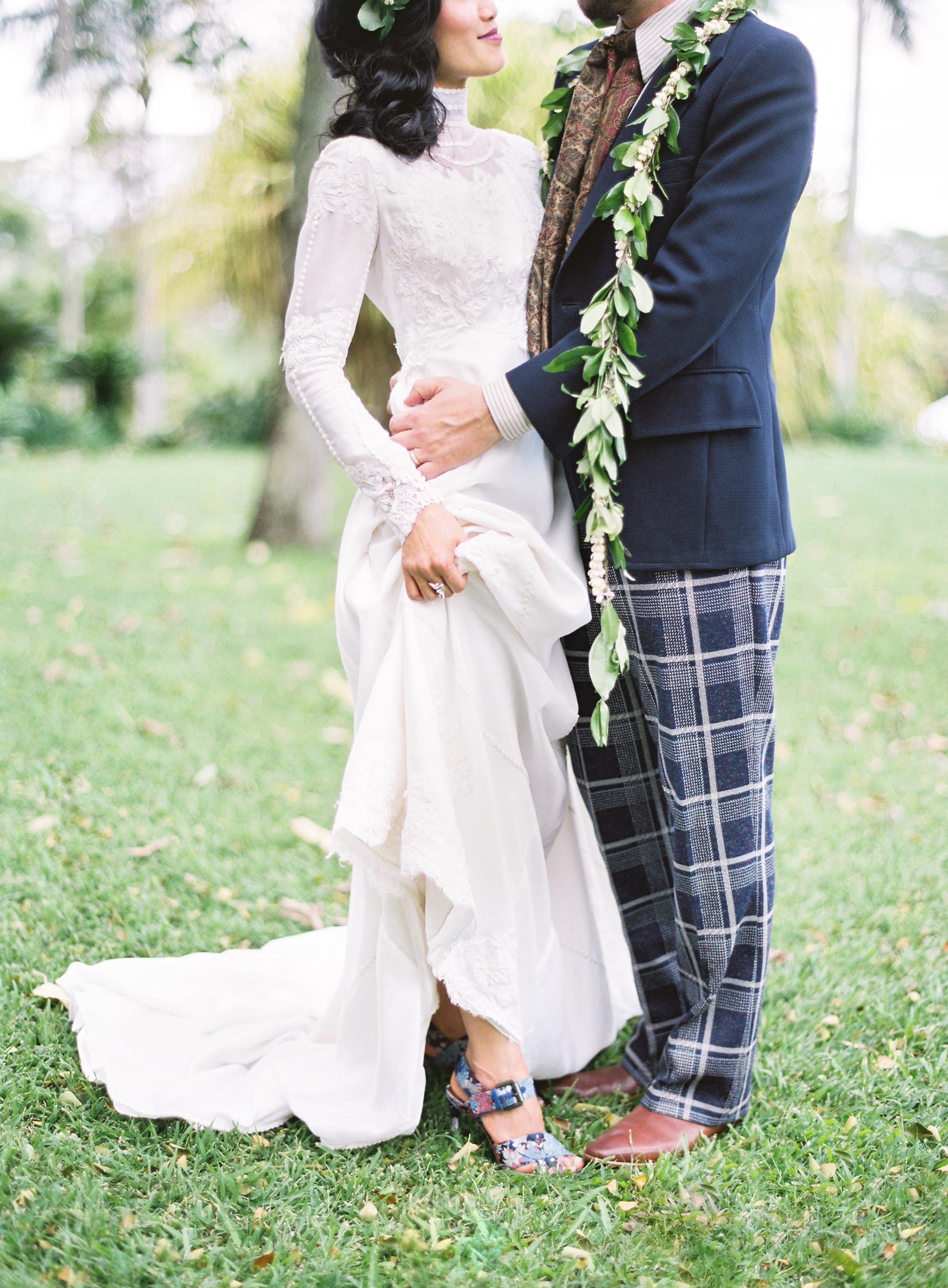 Groom embraces bride, hand around her waist