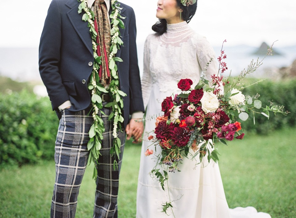 Bride and groom hold hands with floral arrangements on display