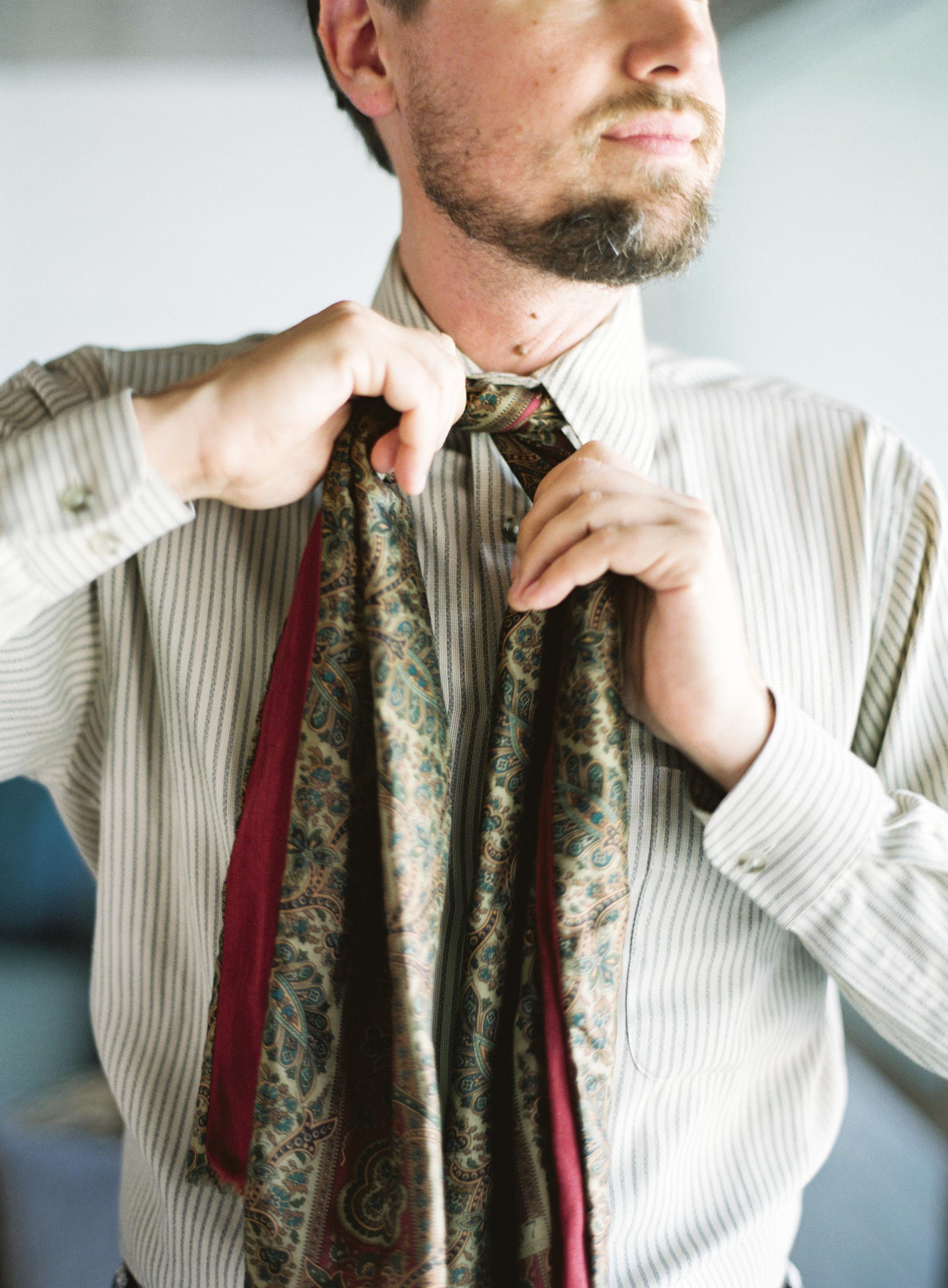 Close-up of groom tying his tie