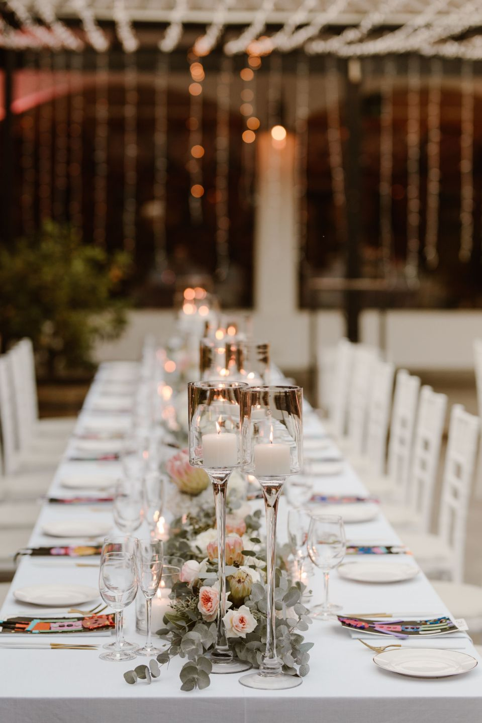 Pictured is the table settings, featuring local florals and candles. The couple wanted minimal, simple wedding decor which incorporated three cultures in an understated style.
