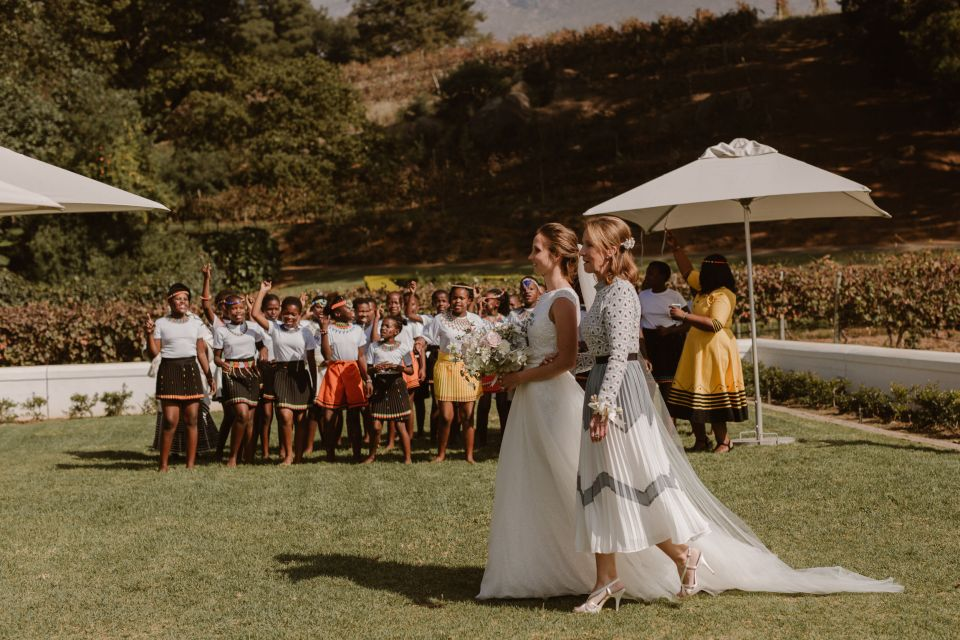 Bride Sophie walked down the aisle with her Mom while the Nondzame school choir sang, another way the bride and groom created a socially conscious wedding was to include uplifting projects from the local community.