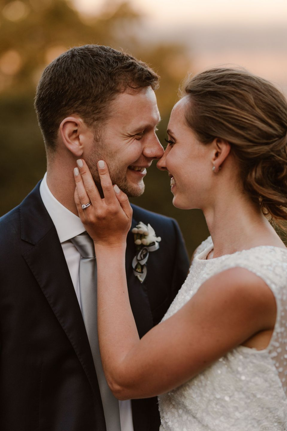 A close up of the bride and groom embracing and smiling.