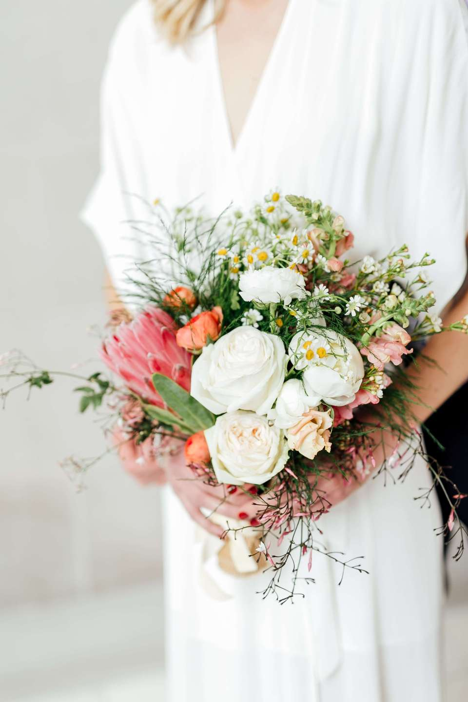 A close up of a bride holding her sustainable wedding bouquet.