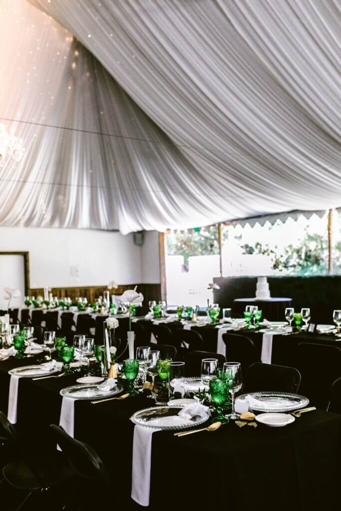 A beautiful setup of a wedding reception with black linen and tables covered in florals.