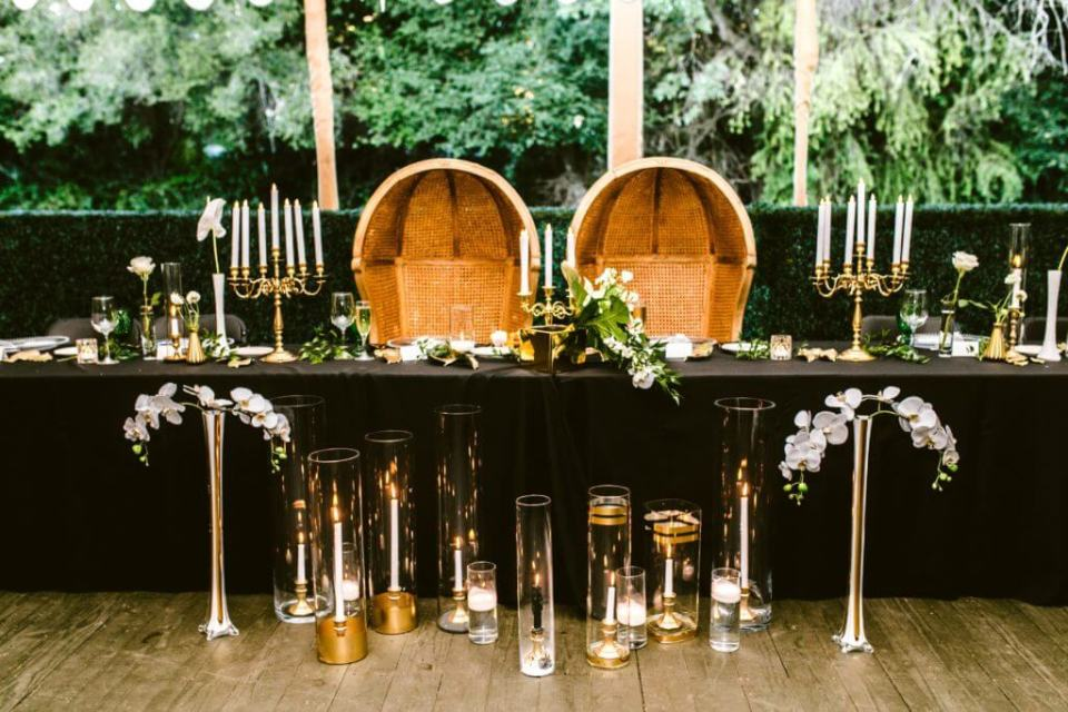 A beautiful design by Amethyst Event Productions, which features a table covered in black linen, and accentuated by candles and florals.