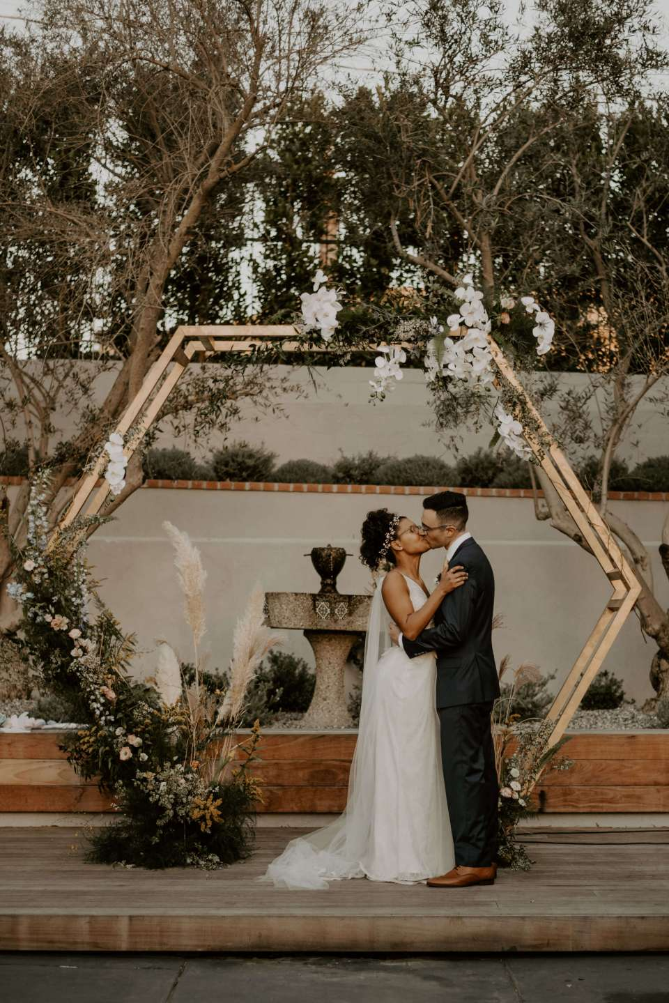 A couple poses in front of a geometric arch on their wedding day, planned by Amethyst Event Productions, who shares their key questions to ask a wedding planner in this post.