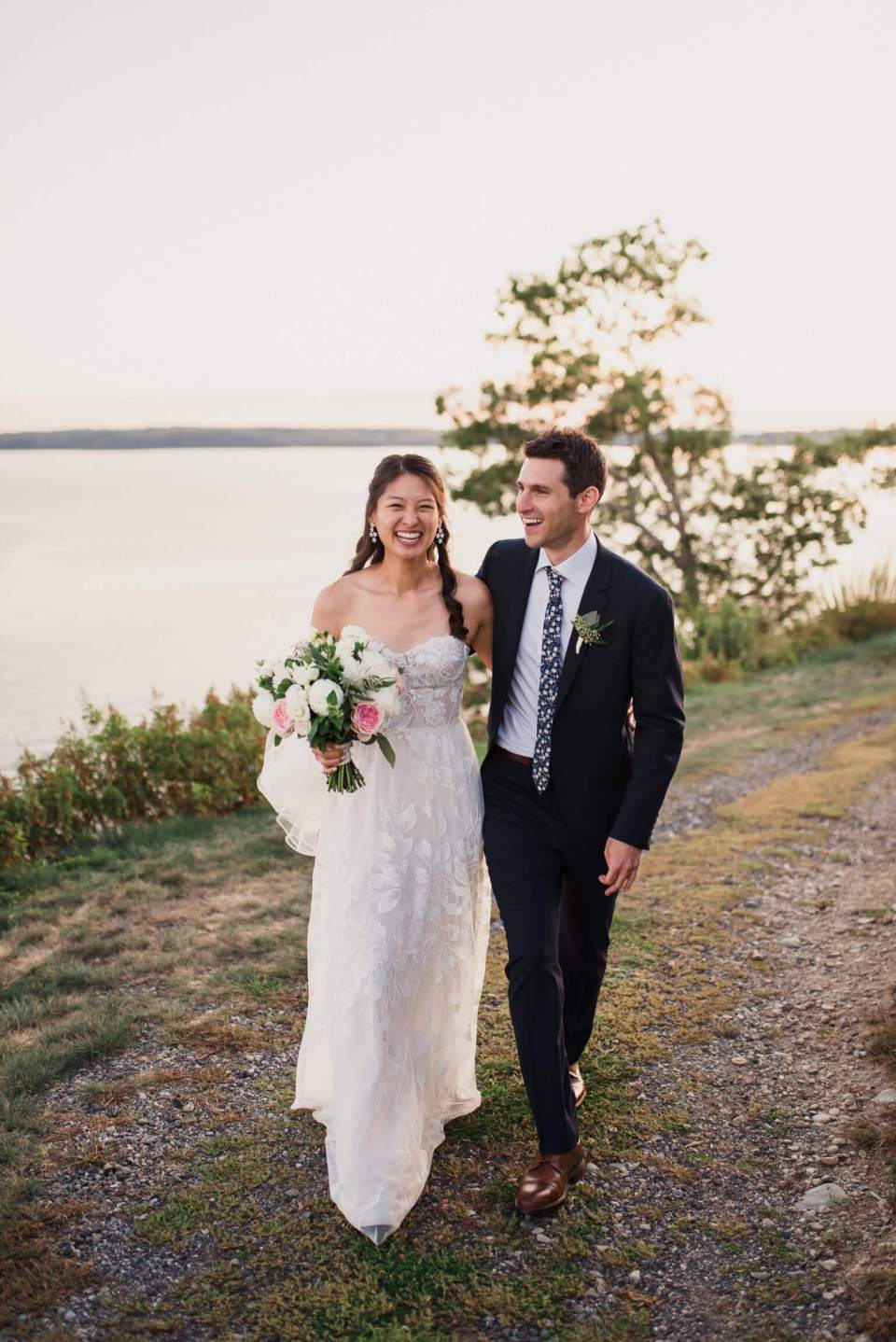 The bride and groom walk by the lake at their wedding.