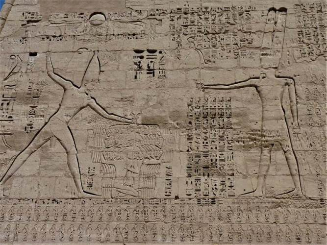 Pharaoh Rameses III holding the hair of his enemies, and the god Amun. Relief from Medinet Habu temple, Luxor. Courtesy of Alyssa Bivins / Wikimedia Commons. https://commons.wikimedia.org/wiki/File:Relief_of_Ramses_III.jpg (image reduced in size from original).