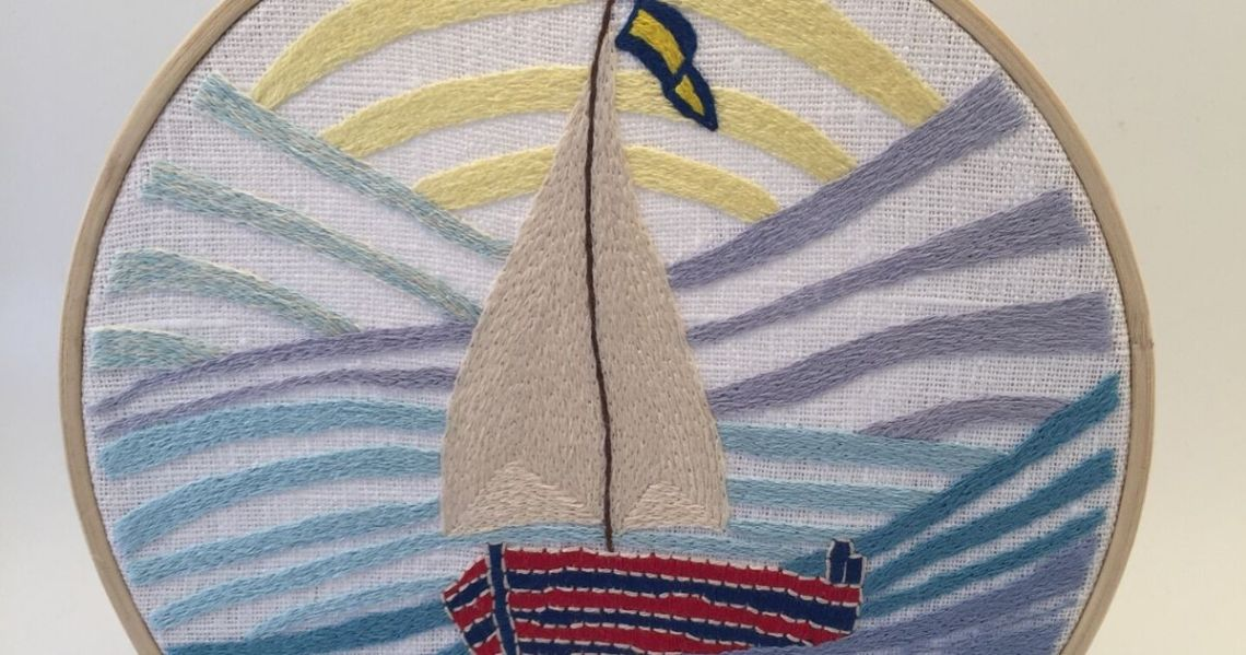 Hand embroidered sail boat with a sail and a flag
