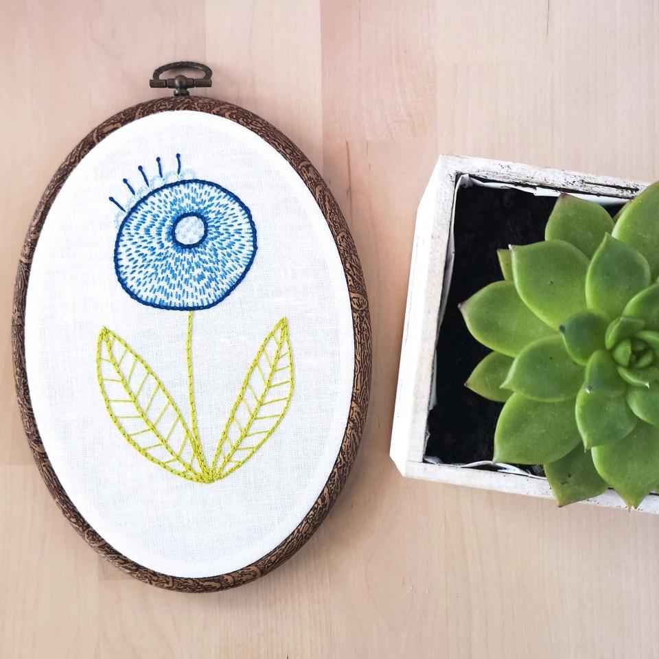 Blue modern flower hand embroidery in an oval hoop