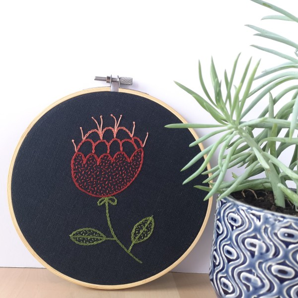 Red abstract flower hand embroidered hoop on navy blue fabric near a succulent plant