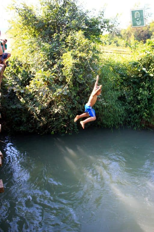 Laotian kids jumping in the water from the bridge