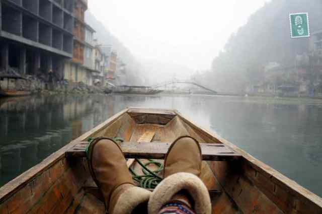 A girl is riding a boat in Fenghuang China