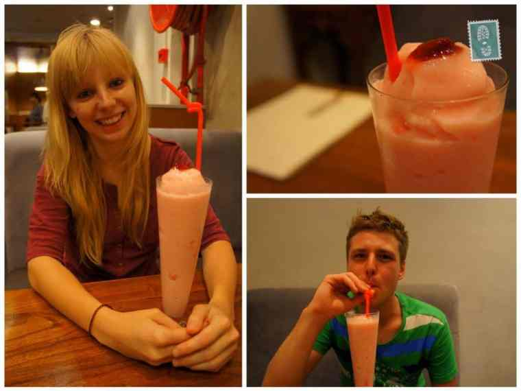 Two people are smiling and drinking a strawberry shake