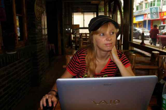 A girl is sitting at the laptop working