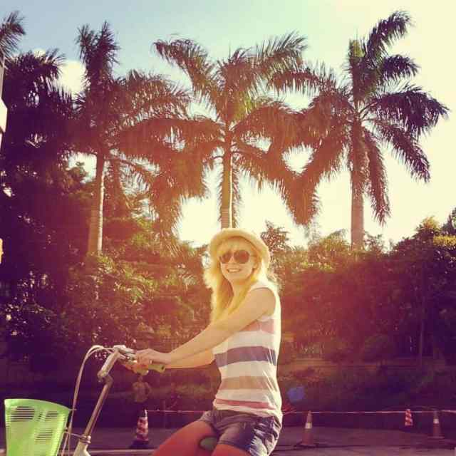 A girl on a bike and palm trees
