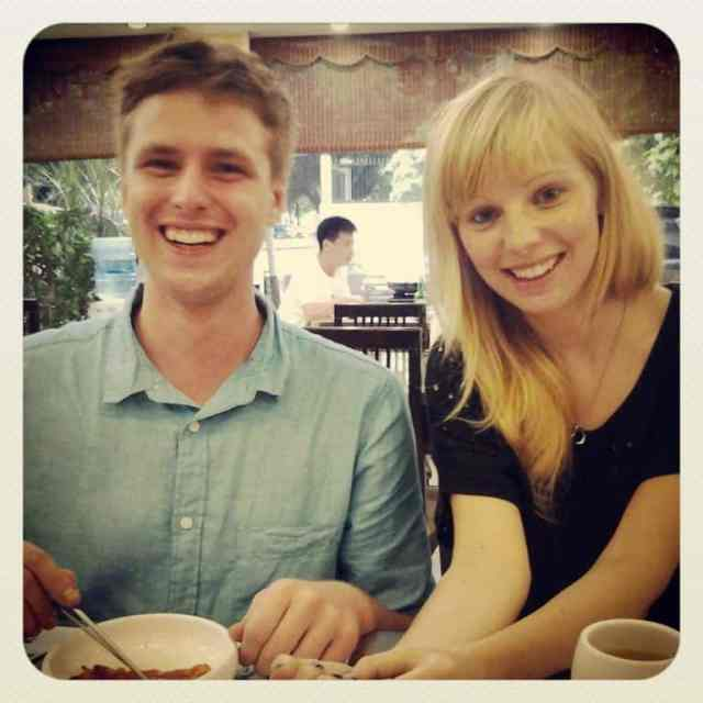 A couple eating a Korean food and smiling