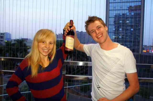 a girl and a boy are celebrating with a bottle of wine