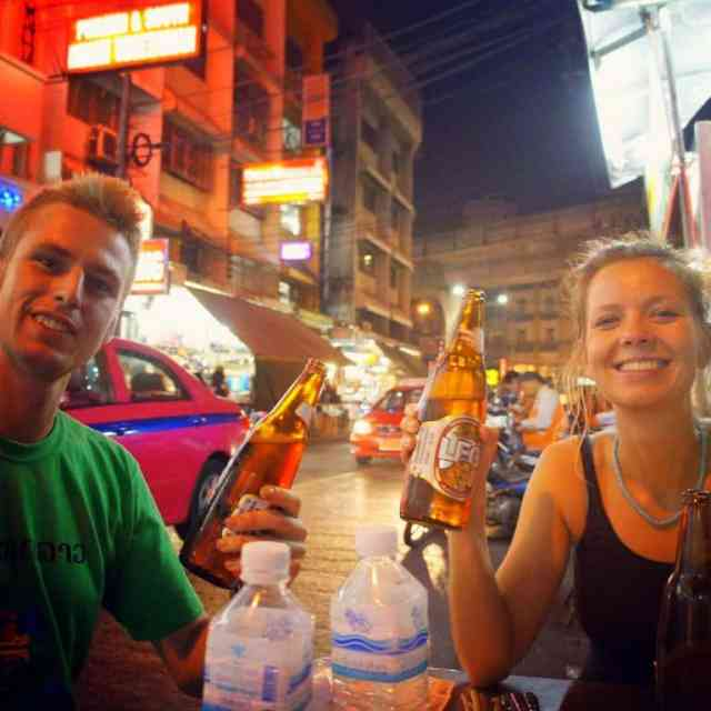 Two people are drinking a Thai beer