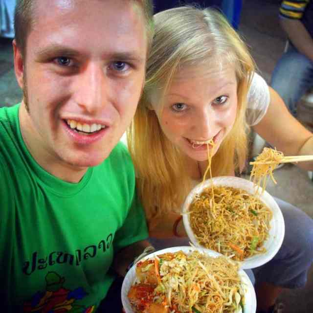 two people are eating pad thai in the street in bangkok