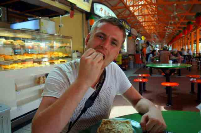 A boy eating roti prata