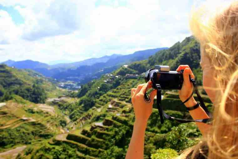 A girl is taking a picture of Banaue Rice Terraces