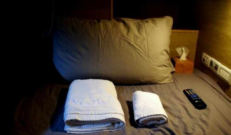 bed, pillow and towels in a hostel