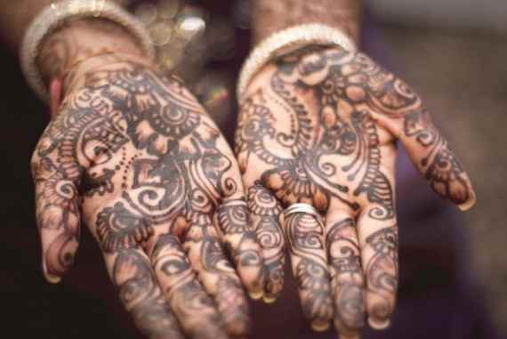 Woman's hands covered with henna patterns