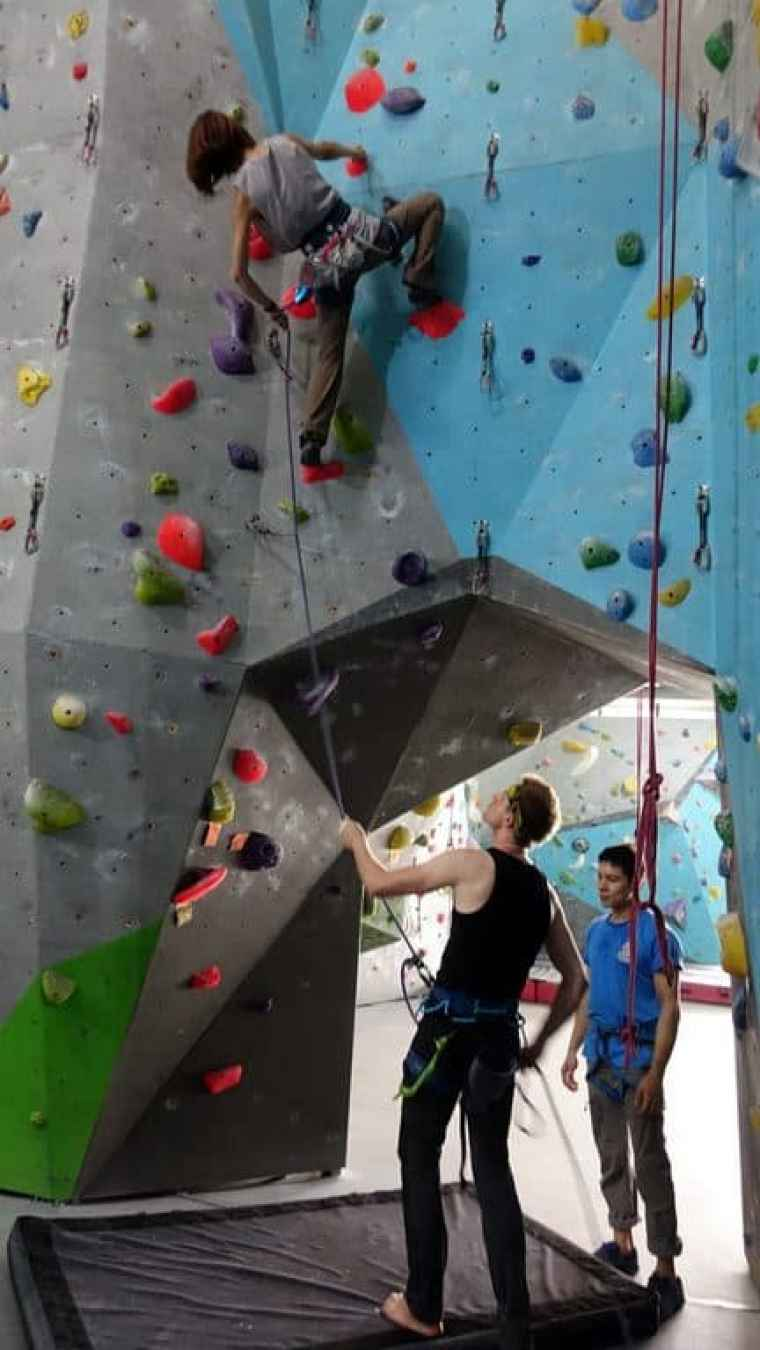 Learning how to belay for Lydia as she scales the climbing wall