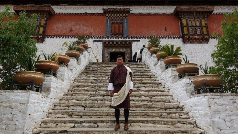 A monk stands in front of a temple, Bhutan Tour Itinerary