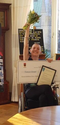 Bildtolkning: Frida sitter i sin rullstol och håller segervisst upp en blombukett. I famnen håller hon ett diplom och en check på 10 000 kr.