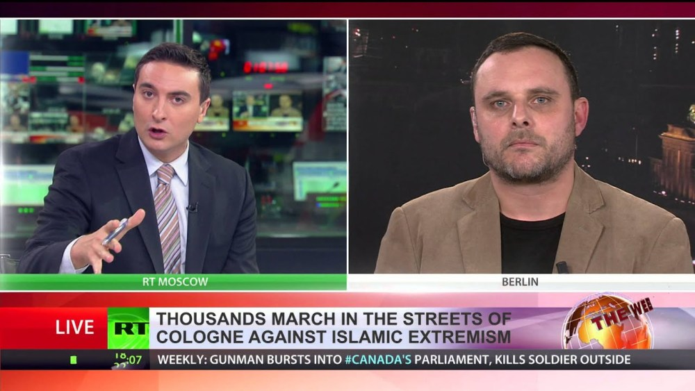 Manuel Ochsenreiter, who has been accused of ordering the firebombing of a Hungarian cultural centre in Ukraine, being interviewed on Russia's RT